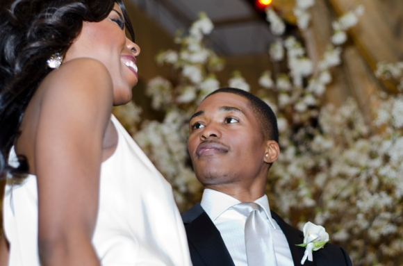 Albert Odusanya smiles at partner, Ryann Richardson, before walking down the runway at the Bellevue Gets Engaged bridal event, featuring bridal gown designs by Nicole Miller. ( Philadelphia Inquirer, March 5, 2012 )