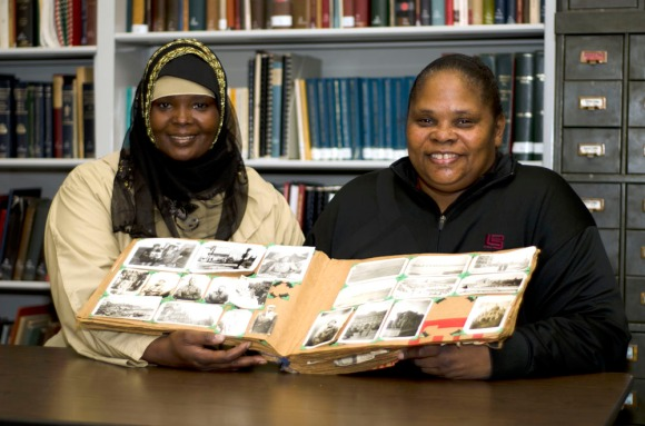 Fatima Johnson (left) holds a book with her mother, Valoree Nelson, containing World War II-era snapshops of African Americans that she found in the trash. ( Philadelphia Inquirer, January 30, 2012 )